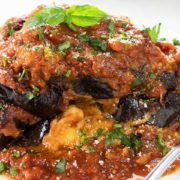 Baked Eggplant Parmesan on a white plate topped with fresh basil
