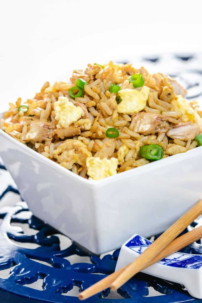 A bowl of fried rice with chop sticks next to it