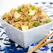A close up of a bowl of fried rice with chop sticks next to it