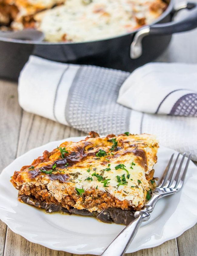A slice of Moussaka on a white plate with the pan in the background