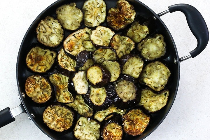 The roasted eggplant arranged in a baking pan