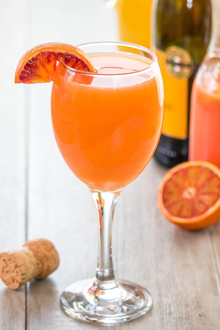 A glass of Mimosa with a wedge of orange on the glass