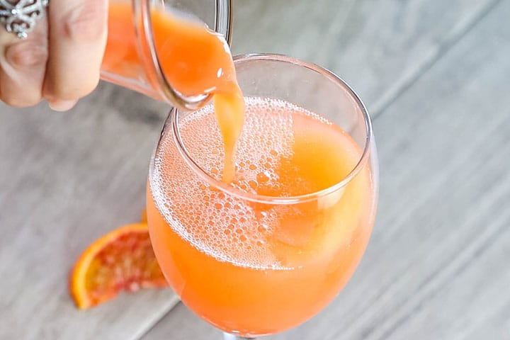 blood red orange juice being poured into the glass with the sparkling wine.