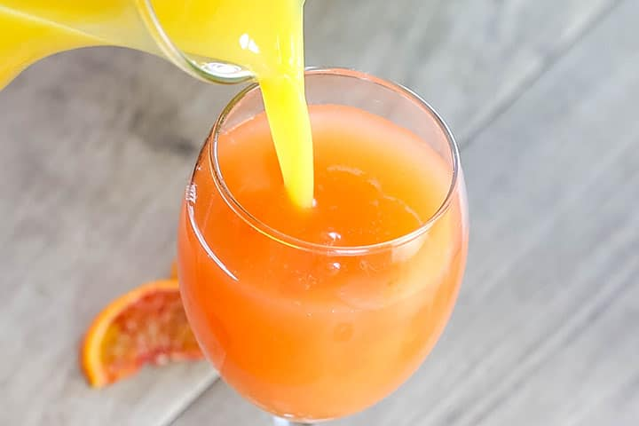 orange juice being poured into the glass with the sparkling wine and blood orange juice