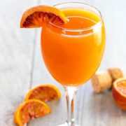 The Perfect Mimosa with a wedge of blood orange on the glass