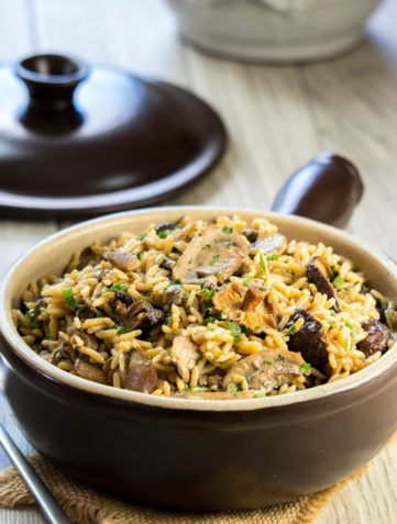 easy mushroom rice pilaf in a serving dish with the lid behind it