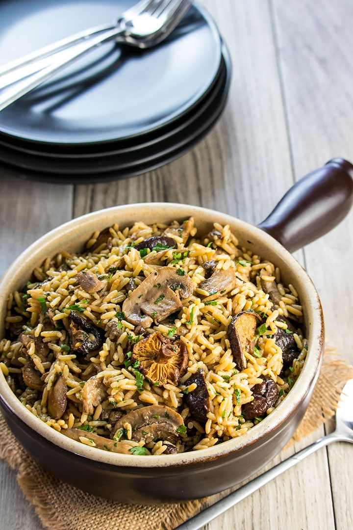 the easy mushroom rice pilaf in a serving dish with plates in the background