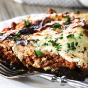 A slice of Moussaka on a white plate and a fork next to it