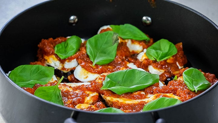 Basil leaves scattered across the top of the eggplant and tomato sauce