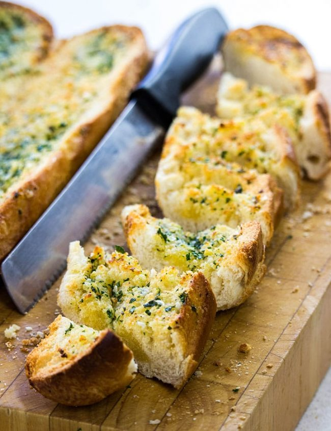 Perfect Garlic Bread sliced on a cutting board with a bread knife next to it