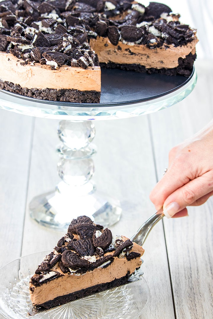 A slice of no bake Oreo cheesecake being served with the cake in the background