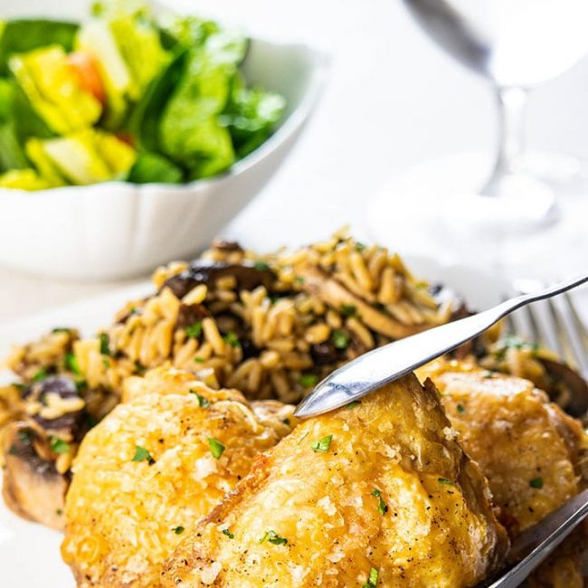 Crispy Oven Baked Chicken Thighs being served on a plate with rice and salad in the background