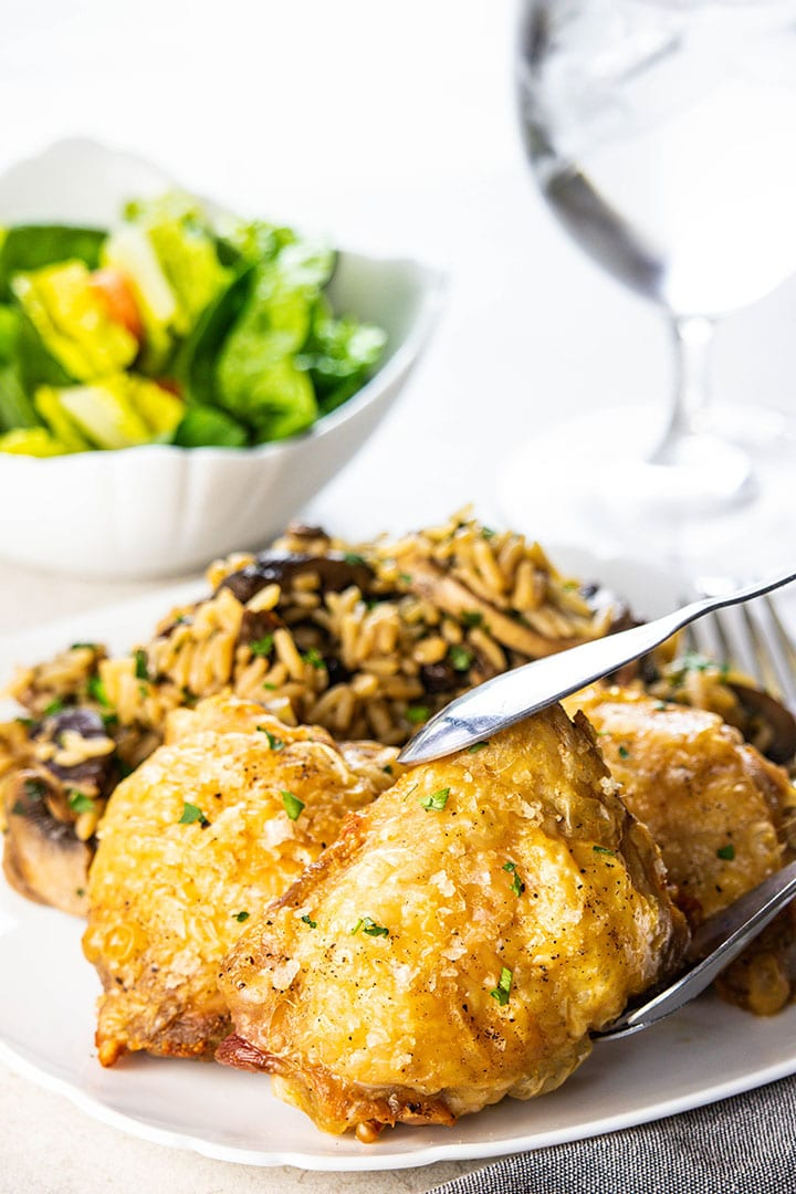 Crispy Oven Baked Chicken Thighs on a white plate with rice and salad in the background