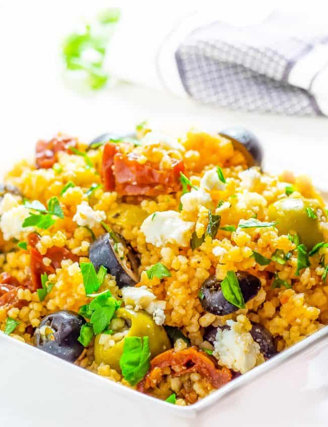 a bowl of couscous with vegetables and olives