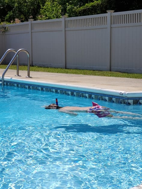 a little boy snorkeling in a swimming pool