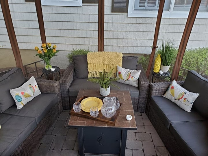 a gazebo with patio furniture and fire pit