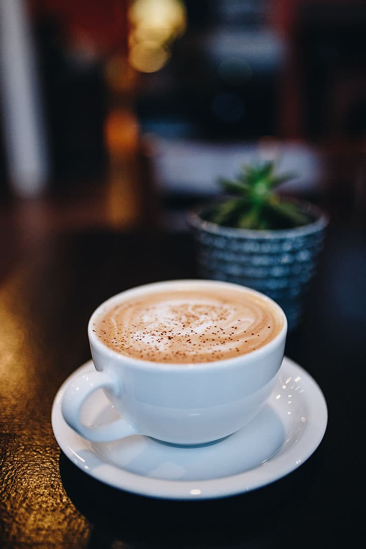 a white cup of cappuccino sprinkled with nutmeg on a dark table