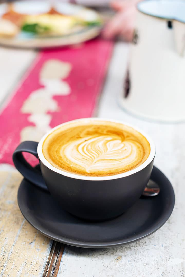 A coffee cup filled with cappuccino on a kitchen table