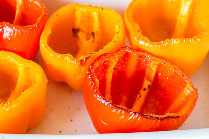The roasted coared peppers in the roasting pan