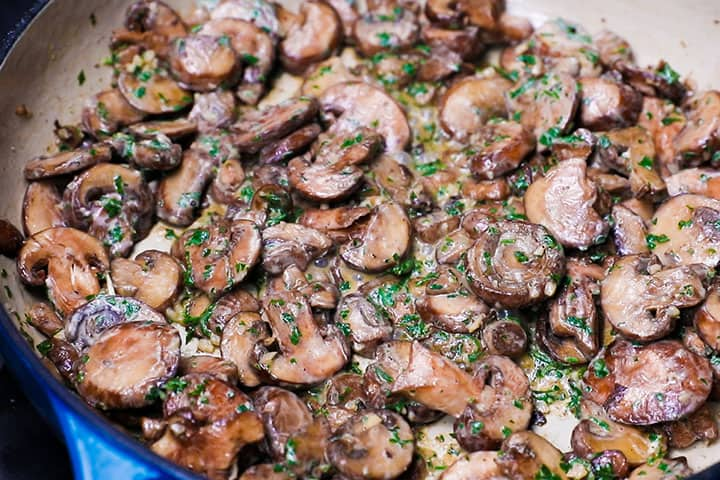 sautéed mushrooms in a pan with sour cream and chopped parsley