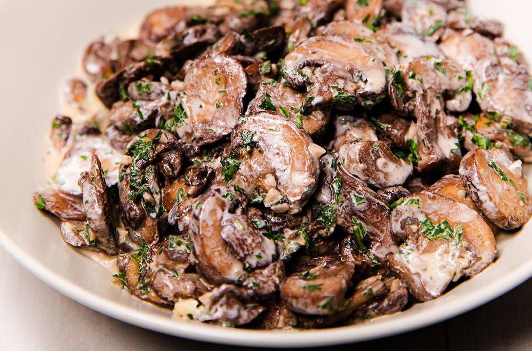 a bowl piled high with creamy garlic mushrooms sprinckled with parsley
