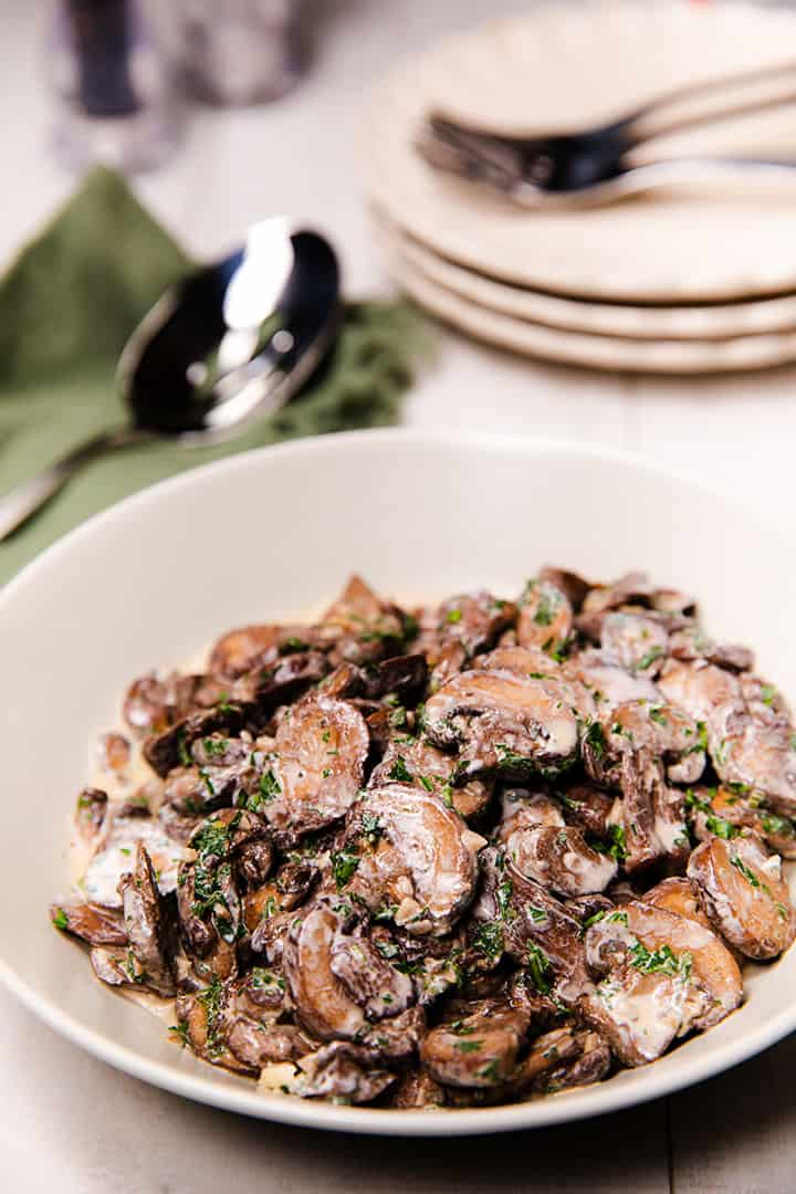 a bowl piled high with creamy garlic mushrooms sprinckled with parsley with plates, forks and a serving spoon in the background