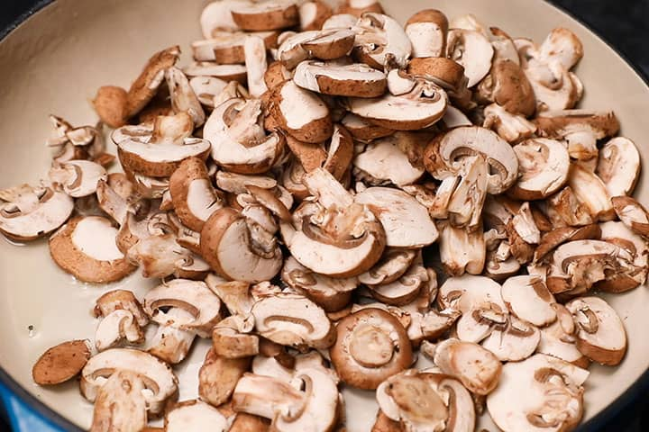 Raw sliced mushrooms in a pan