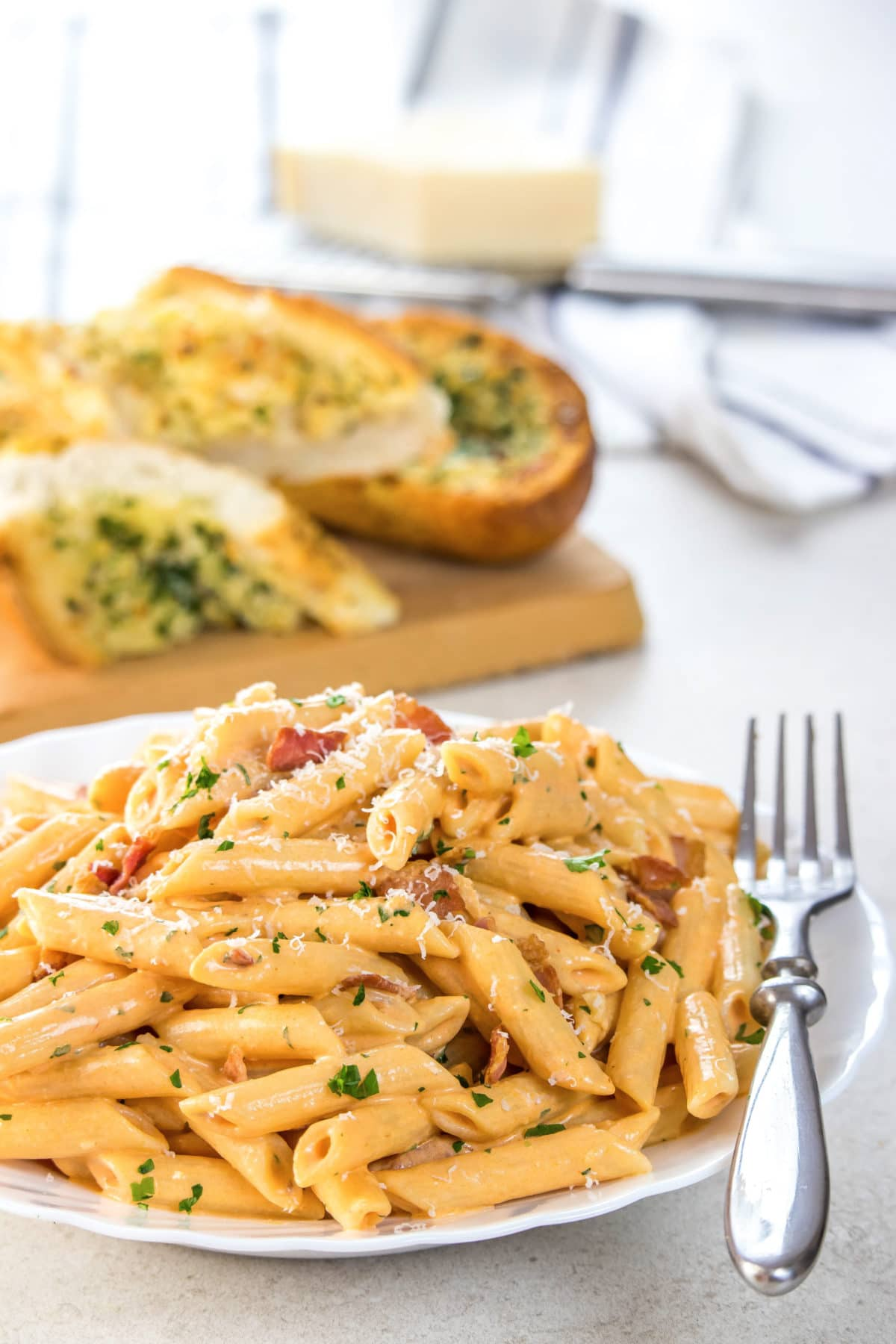 Penne Alla Vodka piled high on a white plate, sprinkled with parmasean cheese anf garlic bread in the background