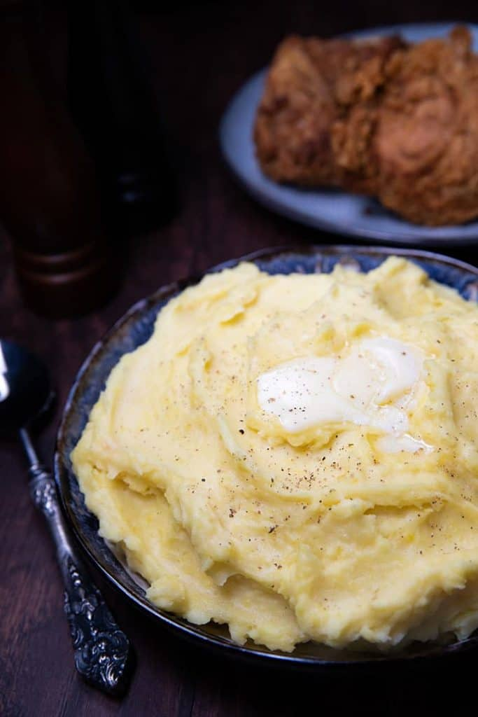 A big bowl of mashed potatoes with butter melting on top