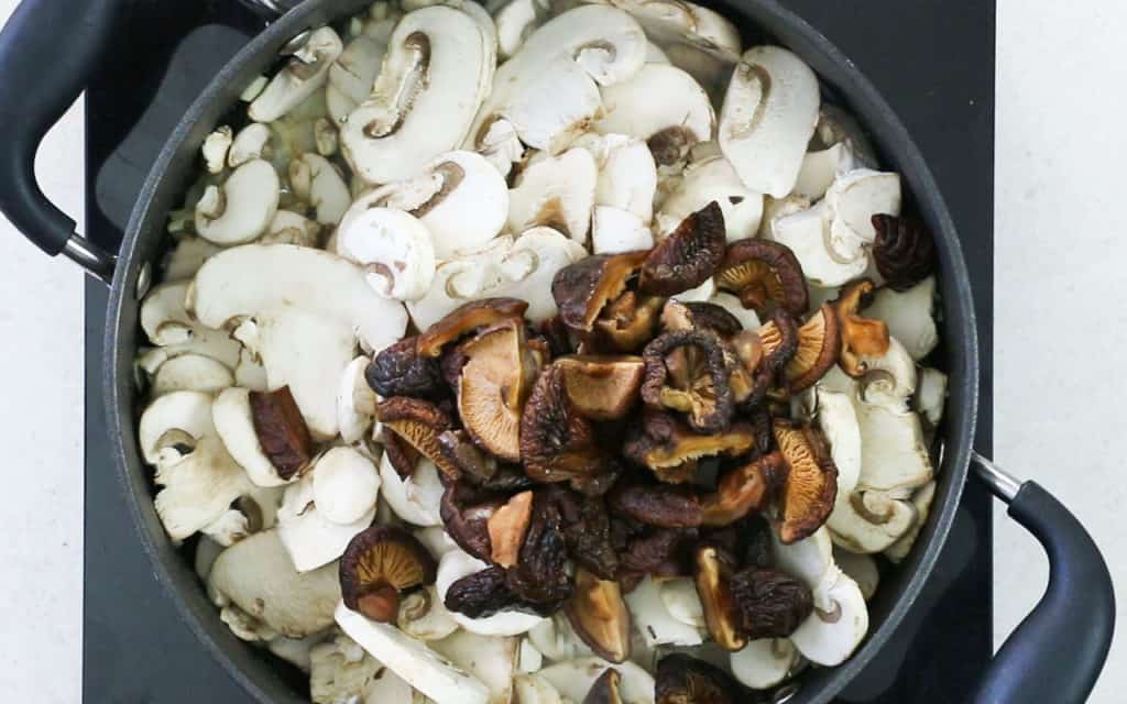 The mushrooms added to the pan with the onions and garlic