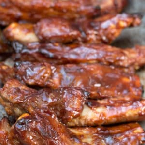 Barbecued sticky glazed ribs on a pan with sauce brushed over then