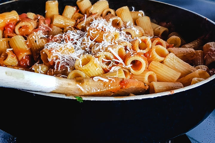 the grated cheese added to the pan with the pasta and sauce
