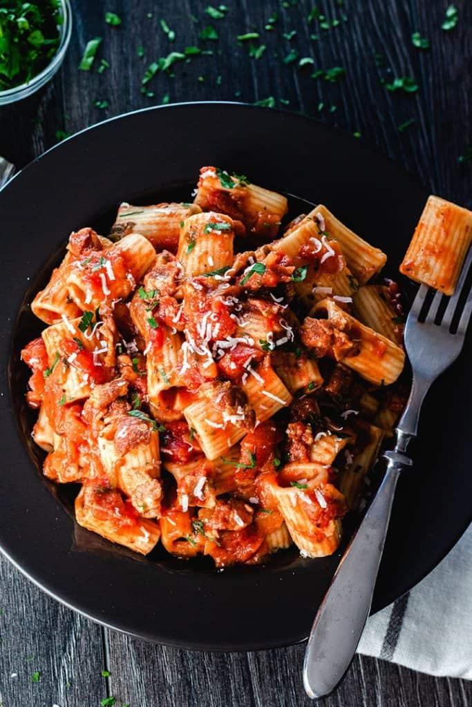 a plate of pasta with Amatriciana Sauce topped with grated cheese and parsley