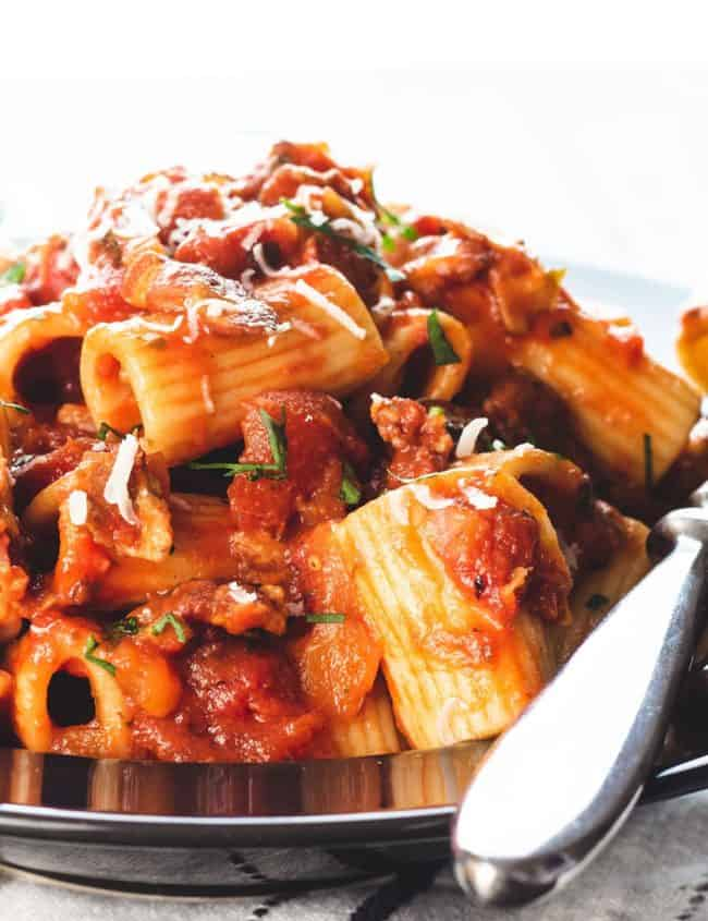 A heaping bowl of pasta with Amatriciana Sauce topped with grated cheese