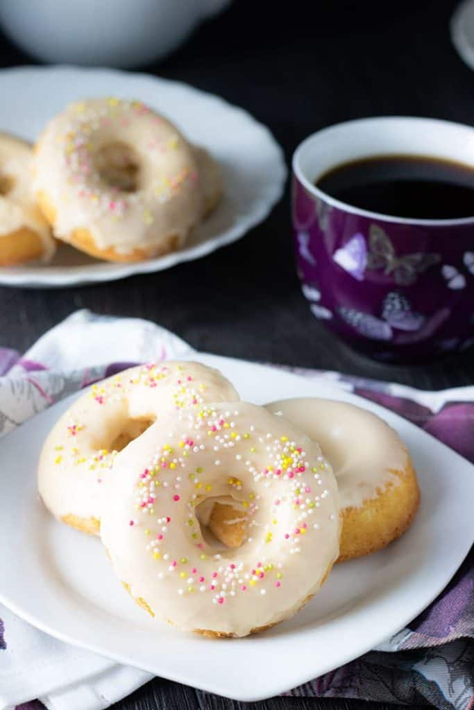 three Baked Vanilla Donuts on a plate with a cup of coffee behind it