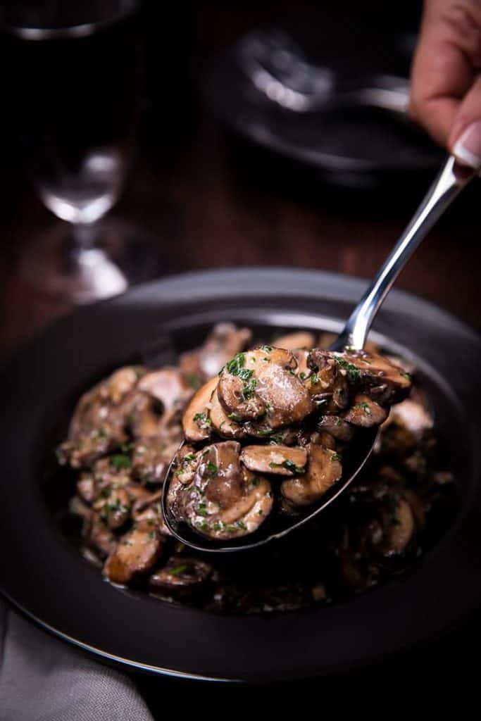 the Easy Sautéed Mushrooms being served with a spoon
