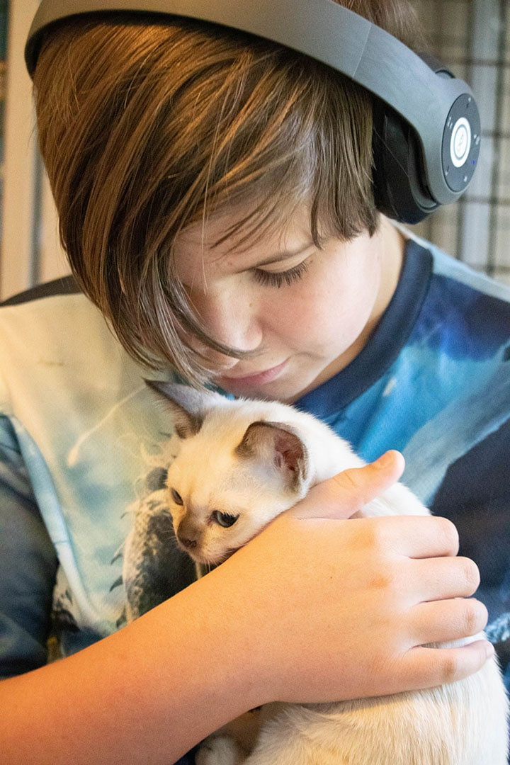Ethan holding a little white cat with a black nose.