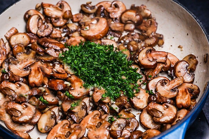 the herbs added to the mushrooms and garlic in the pan
