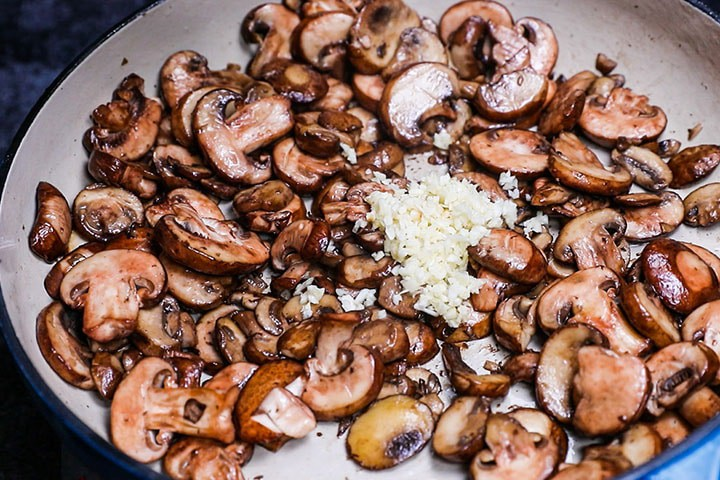 garlic added to the cooked mushrooms in the pan