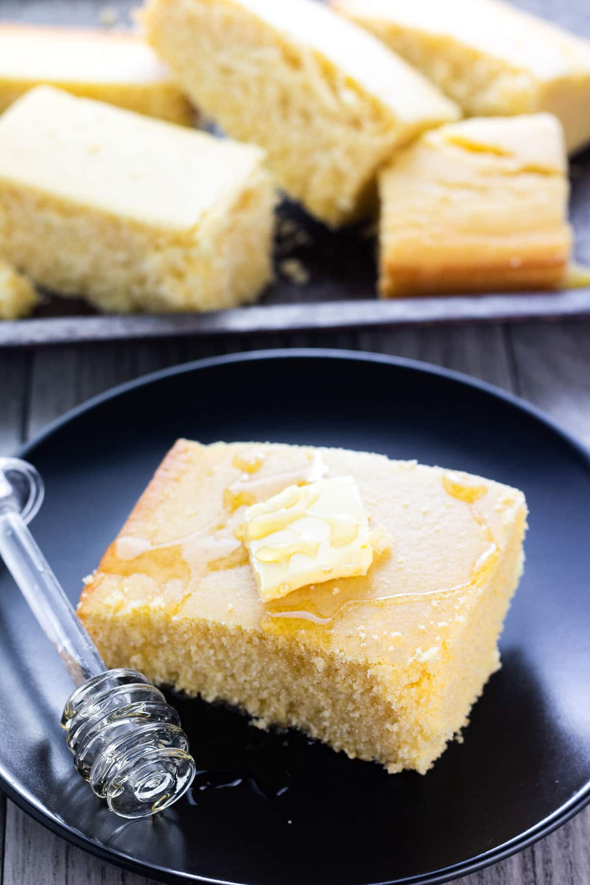 A slice of cornbread on a plate, with butter and honey