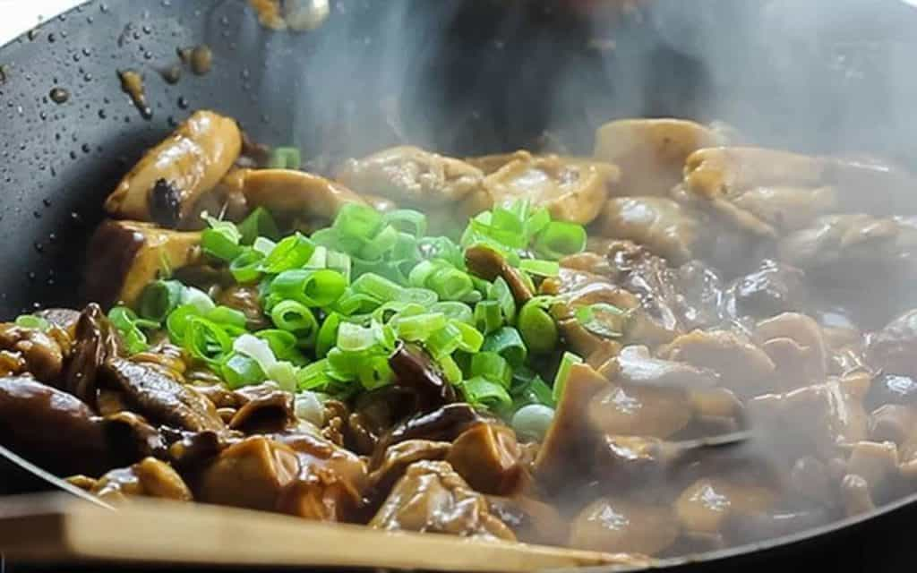 the chicken in the sauce with green onions
