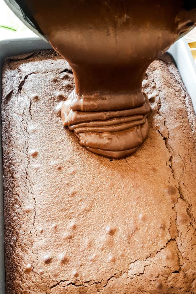 the chocolate fudge being poured onto the cake