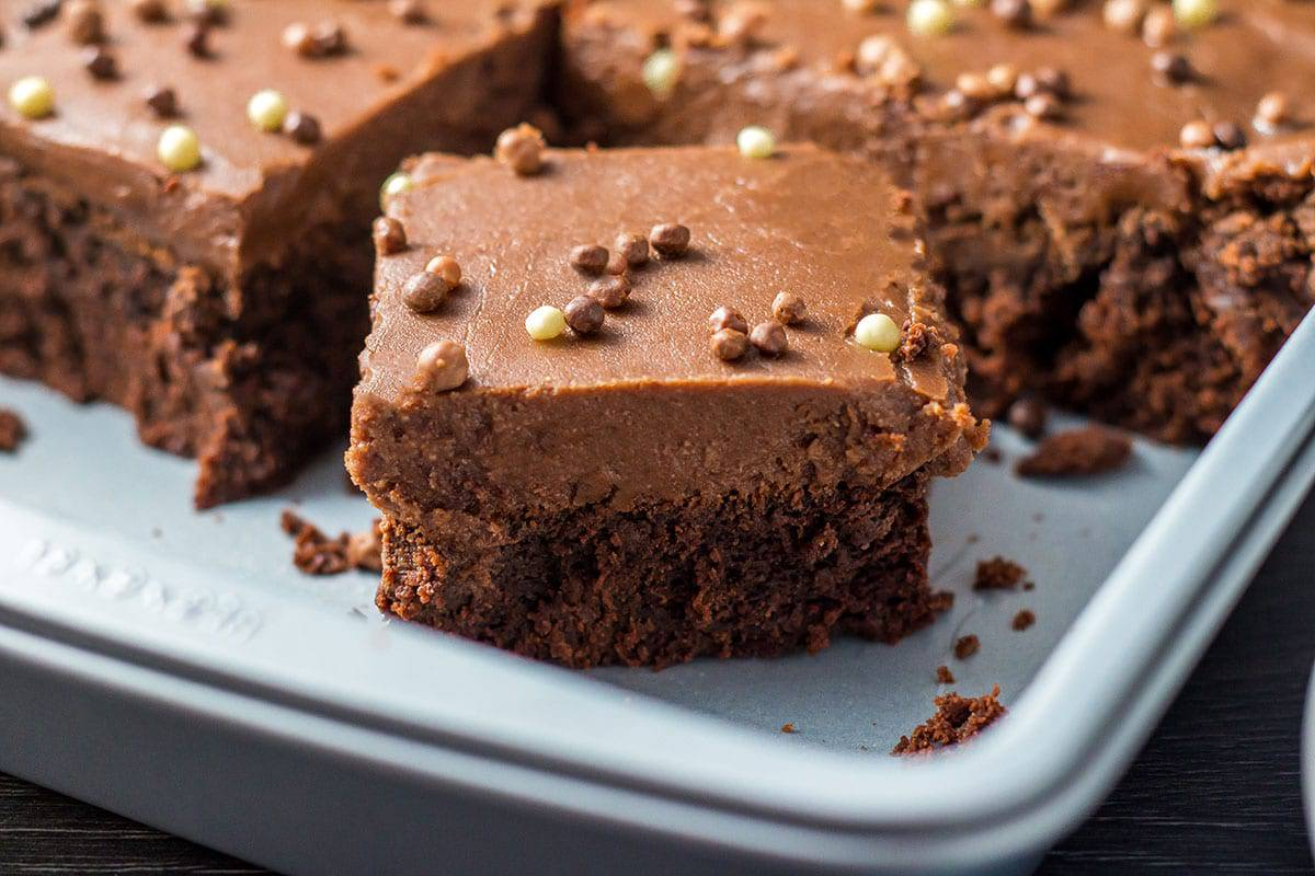 a chocolate fudge sheet cake with a slice cut out of it
