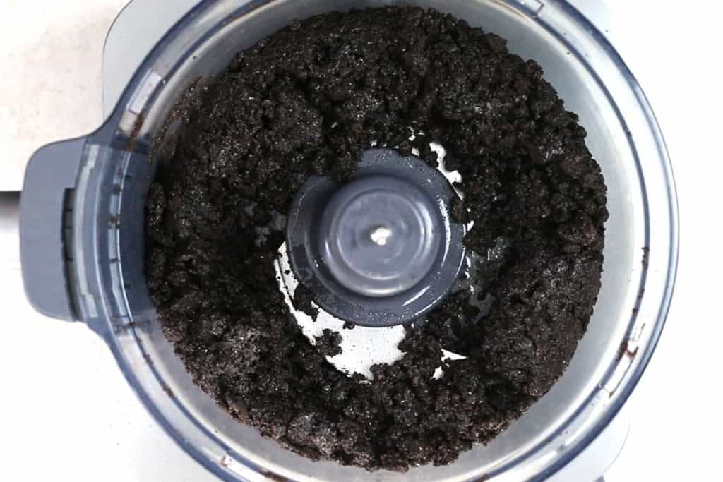 crushed oreo cookies in a food processor coated with melted butter