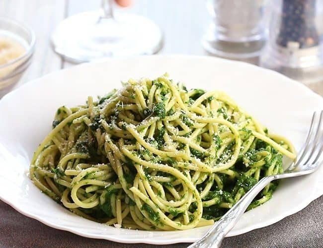 A bowl of Spaghetti with Spinach Sauce with a fork next to it on the plate