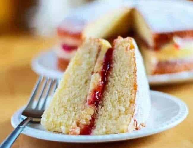 Slice of Victoria Sponge Cake filled with buttercream and raspberry jam on a plate