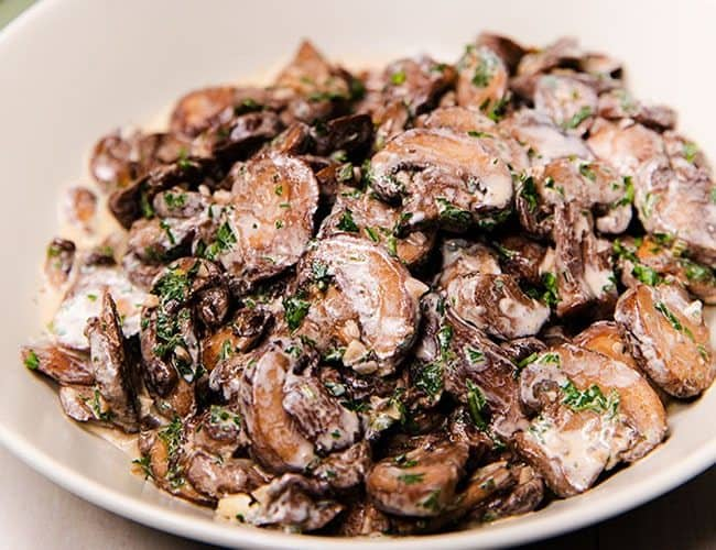 Creamy Garlic Mushrooms in a cream colored serving dish