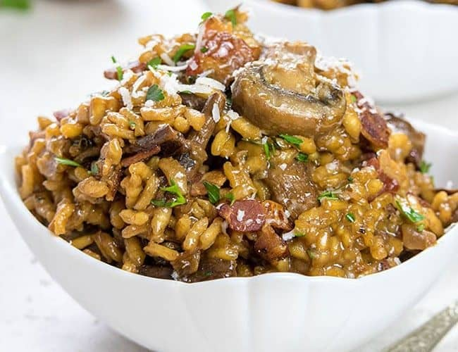 Easy Mushroom & Bacon Risotto piled high in a white bowl