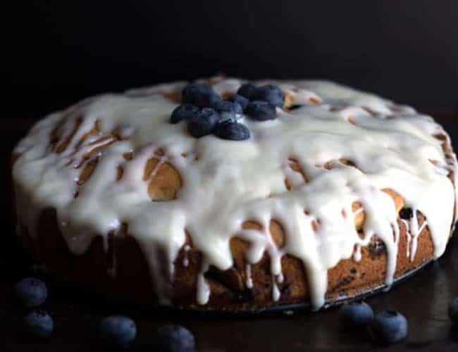 The Best Blueberry Cake EVER on a cake plate topped with fresh blueberries