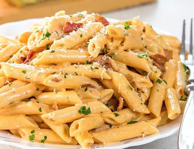 Penne Alla Vodka piled high on a white plate, sprinkled with parmasean cheese.